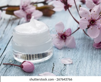 natural facial cream with beauty  cherry blossoms on wooden background