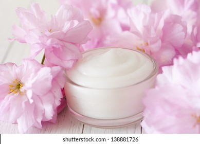 natural facial cream with beauty japanese cherry blossoms on white wood