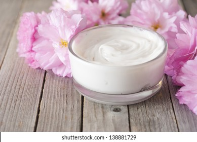 natural facial cream with beauty japanese cherry blossoms on wood