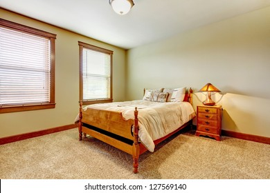 Natural farm house bedroom with beige carpet and green walls.