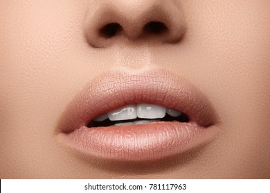 Natural fashion lipstick. Close-up of a beautiful sexy lips. Nice full lips with lip makeup. Filler Injections. Make-up, Plastic Surgery, Collagen and Treatments