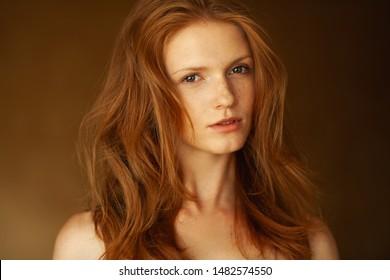 Naturschönheitskonzept für Frauen. Portrait des jungen Models mit rotem, gewelltem Haar, natürliches Make-up auf goldenem Hintergrund. Reine Haut mit Sonnenflecken. Tageslicht. Retro-Stil. Nahaufnahme. Studioaufnahme