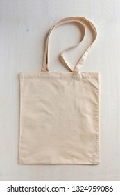 Natural fiber neutral coloured re-usable shopping bag with handles laid flat on a white background