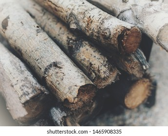 Natural fire wood logs covered in bark stacked up in a rack beside an outdoor backyard firepit