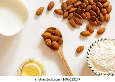 天然の粉、油、アーモンドの種乳をガラスの鉢に入れたもの。白い背景に木のスプーンにナットのアーモンド。