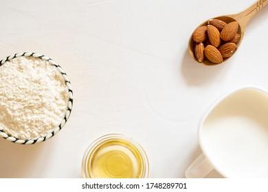 天然の粉、油、アーモンドの種乳をガラスの鉢に入れたもの。 白い背景に木のスプーンにナットのアーモンド。