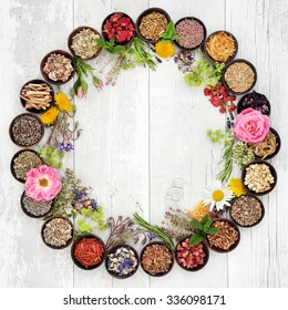 Natural flower and herb selection used in herbal medicine in bowls and loose forming a circle over distressed wooden background.