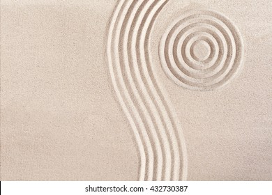 Natural flowing wave form and concentric circles raked in the smooth sand in a Japanese Zen Garden portraying tranquility and meditation in a wellness concept