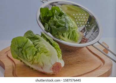 Natural food produce,two little gem lettuces,one is inside a colander,the other on a wooden chopping board,there is a white grey background.