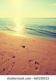 Natural footprints in beach sand. Traces on beach by smooth sea, coastline in summer