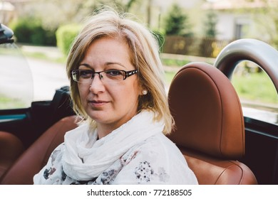 Natural forty years old woman in cabriolet car