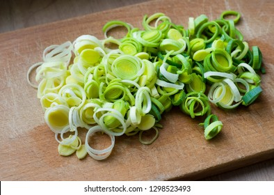 Natural fresh cutted leeks on the wooden cutting board. Leek cut by means rings on a chopping board. Closeup of sliced fresh green leek. Fresh vegetables. Cooking healthy food. Selective focus.