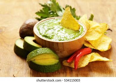Natural fresh guacamole dip with avocado and corn chips.