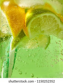 A natural fruit background with macro lime slices, lemon and a colored drinking plastic straw in a glass jar with aerated gassed bubbles. Concept of cold alcoholic or non-alcoholic summer drinks.