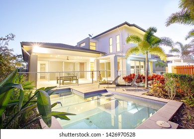 Natural garden with pool in luxurious house, garden have flower trees and green plants, two metal chairs on the tile floor, evening time scene with colourful lights, modern house outdoor garden.