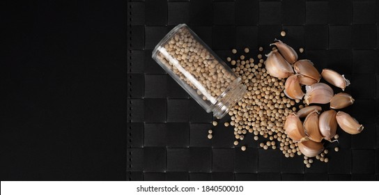 Natural Garlic and white peppercorn in glass bottle on plate mat black background in studio shot. It is main ingrediant for many asian recipe menu such as Singapore Bak kut teh, Thailand's Pad Thai