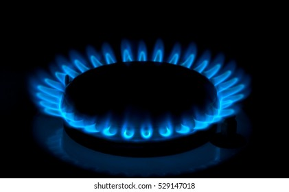 Natural gas burning a blue flames on black background.