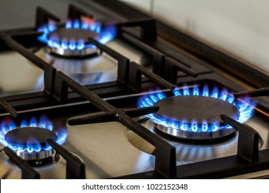 Natural gas burning on kitchen gas stove in the dark. Panel from steel with a gas ring burner on a black background, close-up shooting.