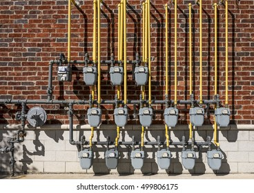 Natural gas meters with yellow supply lines hang on a wall outside a brown brick building.