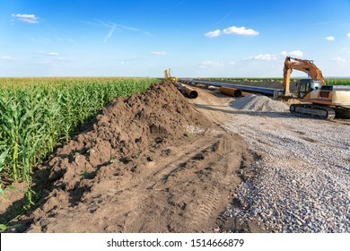 Natural Gas Pipeline Construction in Cultivated Agricultural Farm Field. Heavy Machinery and Gas Pipeline Construction Site. Pipes are Laid on Top of Supportive Sandbags and Welded Together.