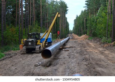 Natural gas pipeline construction work. A dug trench in the ground for the installation and installation of industrial gas and oil pipes. project. Crawler crane with side boom or pipelayer bulldozer