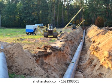 Natural gas pipeline construction work. A dug trench in the ground for the installation and installation of industrial gas and oil pipes. Crawler crane bulldozer with side boom or pipelayer