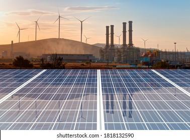 Erdgasaufbereitungsanlage mit Windturbinen für erneuerbare Energien, die bei Sonnenuntergang die Reflektion von Solarpaneelen erzeugen - Industriekonzept