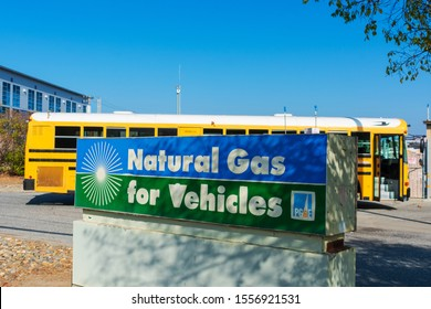 Natural gas school bus fueling behind natural gas for vehicles sign at compressed natural gas CNG fueling station by PG&E, Pacific Gas and Electric Company - San Carlos, CA, USA - 2019
