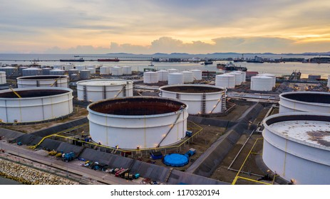 Natural gas storage tanks and oil tanks in oil refinery plant at industrial zone at sunset.