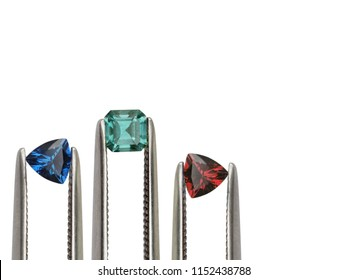 Natural gemstone ; Blue sapphire trillion shape, Emerald asscher shape and Ruby trillion shape held by tweezers macro shot on white background