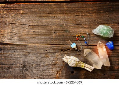 Natural gemstones, white sage and dowsing tool on wooden board