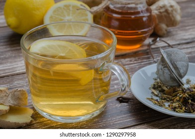 Natural ginger herbal tea in a glass cup and a lternative remedies to treat cold and flue: ginger, lemon, honey and spice.Traditional medicine and natural health care concept.