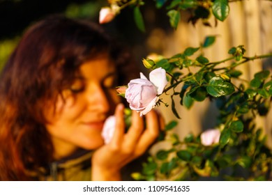 natural girl holding a rose flower in a gentle gesture.