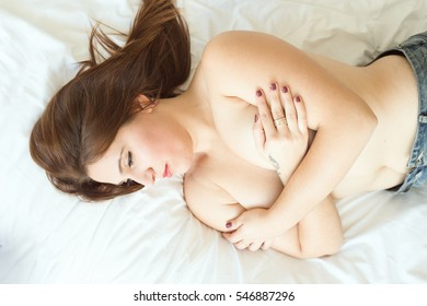 Natural girl poses in bed in her room, shirtless