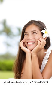 Natural girl smiling and daydreaming. Cute young woman thinking happy looking up outside in summer dress with adorable flower in her brown hair. mixed race Asian Caucasian girl on Hawaii, USA.