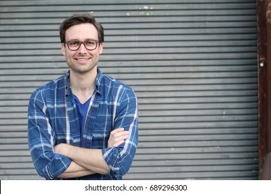 Natural good looking young man smiling with arms crossed and space for copy