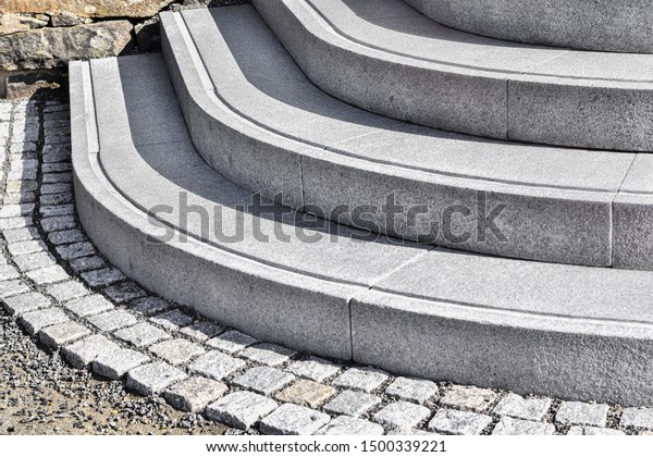 Natural granitt stone stairs and natural grey cobblestones abstract steps, stairs in Norway, granite stairs, common stone steps in monuments and landmarks under the sunny day.