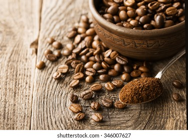 Natural ground coffee heap in transparent glass bowl on ��offee grains background