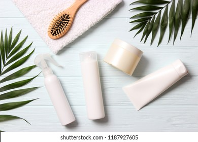 natural hair care products, hairbrush, towel and leaves on a wooden background top view. Shampoo, mask, balm. flatlay