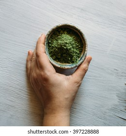 natural hair dye, ceramic bowl with a green pigment, basma green on a white background, green pigment.