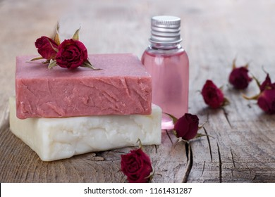 Natural hand made soap with dry pink roses on vintage wooden background spa setting