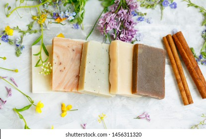 Natural handmade soap bars with organic medicinal plants, cinnamon spice and flowers.Homemade beauty products with natural essential oils from plants and flowers, top view closeup photo