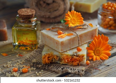 Natural handmade soap with calendula (pot marigold) and sea-buckthorn on rustic wooden background