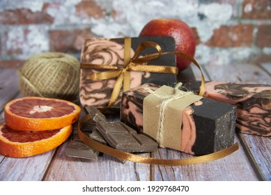 Natural handmade soap with chocolate and orange on a wooden countertop. Healthy lifestyle, eco-friendly products.