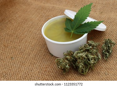 Natural healing cannabis plant hemp ointment salve balm in white cosmetic cup on canvas
