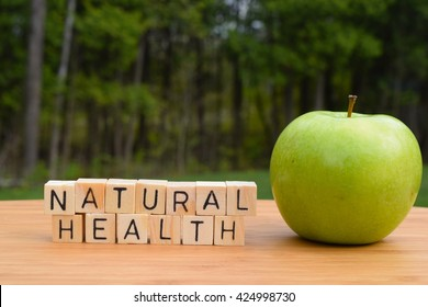 "Natural Health Concept - The words ""natural health"" next to a green apple with a forest background."