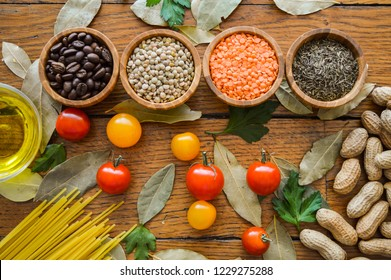 Natural healthy food. Four bowls with spices, coffee beans and lentils on a background on wood table. Top view. Concept about food and healthy fresh ingredients