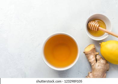 Natural herbal beverage with lemon, honey and ginger on concrete table.