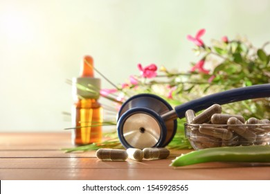 Natural herbal medicine capsules on wood table with stethoscope plants and bottle with medicinal liquid and green background. Alternative natural medicine concept. Front view. Horizontal composition.