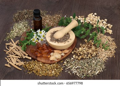 Natural herbal plant medicine used to heal anxiety and sleeping disorders with mortar and pestle and essential oil bottle on oak background.